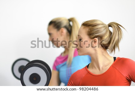Two healthy young women on light background working out in the gym lifting dumbbells. - stock photo