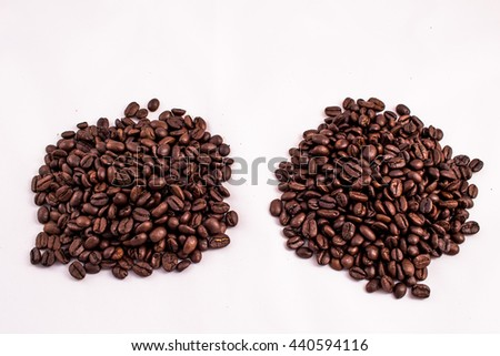 Two heaps of coffee beans. Texture of the coffee beans on a white background. Smelly, saturated brown arabic coffee beans - stock photo