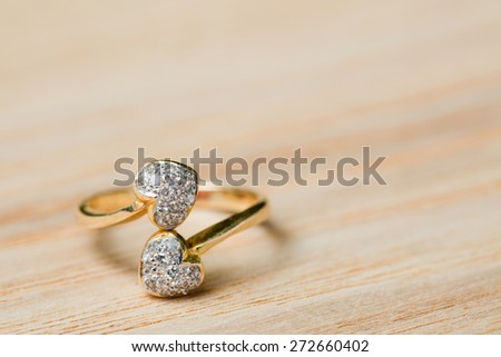 Two heart diamond ring on wood background - stock photo