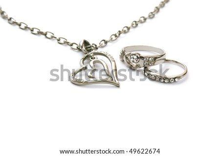 Two heart necklace and rings isolated on white background.
