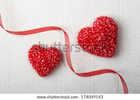 Two heart-shaped candles separated by a red ribbon. Valentine da - stock photo