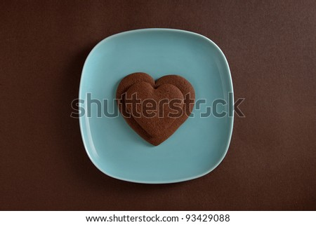 Two heart shaped chocolate cookies on a plate - stock photo