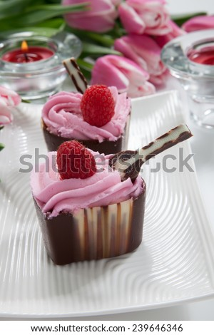 Two heart shaped chocolate cups deserts filled with raspberry cream and garnished with fresh raspberry. Desert for Valentine Day. Bouquet of spring pink tulips and candles.  - stock photo