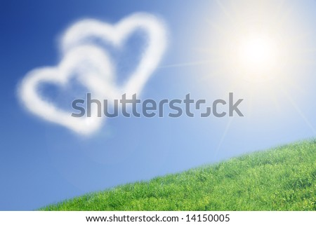 Two heart-shaped clouds in the clear blue sunny sky - stock photo