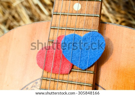 Two heart symbol, red and blue, together under the strings of the guitar. The concept of combining romance and musical creativity - stock photo