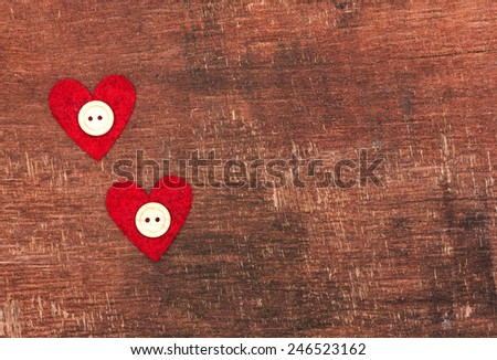 Two hearts and buttons on old shabby wooden background - stock photo