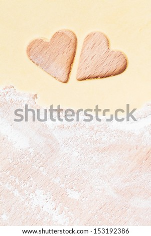 two hearts cutted out of dough near the border with flour on wood - stock photo