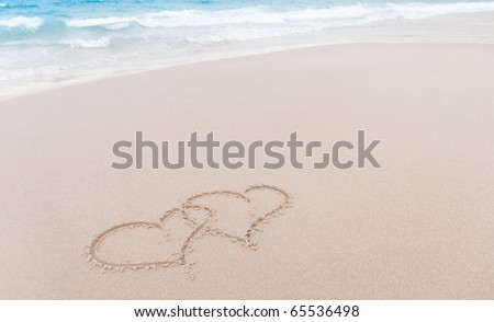 Two hearts drawn in the sand at the beach - stock photo