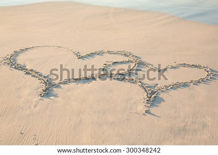 two hearts drawn in the sand on the beach - stock photo