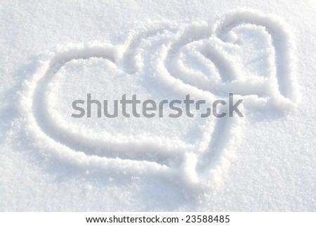 Two hearts drawn on white-blue snow - stock photo