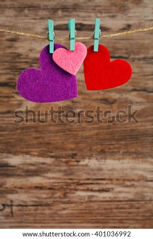 two  hearts hanging on a cord on a wooden background, love background - stock photo