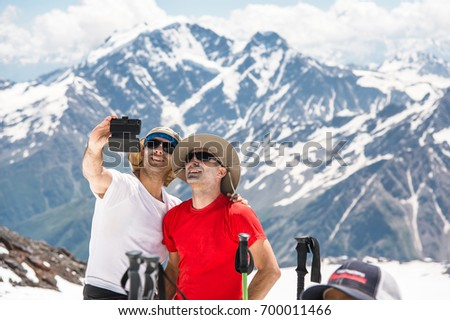 Two hickers taking selfie in the snow-capped mountains against the background of rocks and glaciers