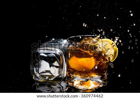 Two high quality glasses of whiskey, one lies on side and other with lemon slices and ice and many splashes on black background.