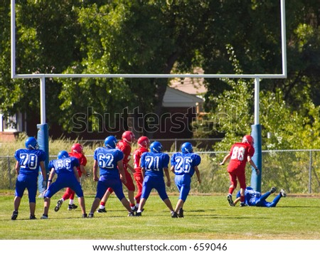 Two high school boys football teams face off and blue scores the touchdown. - stock photo