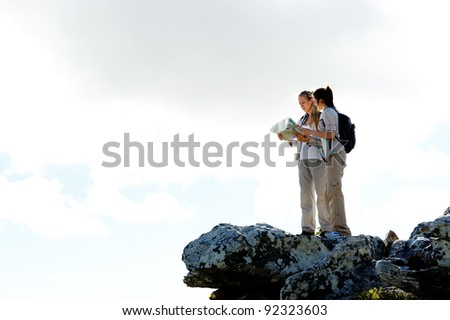 two hikers look at a map while on top of a summit