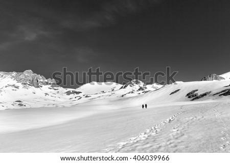 Two hikers on snow plateau (black and white). Turkey, Central Taurus Mountains, Aladaglar (Anti-Taurus), plateau Edigel (Yedi Goller).  - stock photo