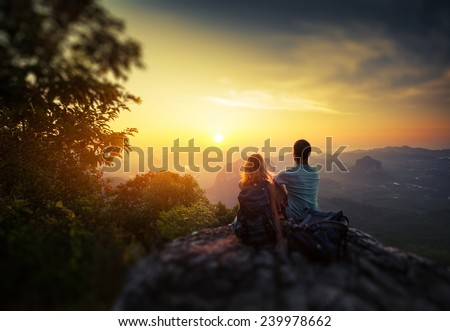 Two hikers on top of the mountain enjoying sunrise over the tropical valley. - stock photo