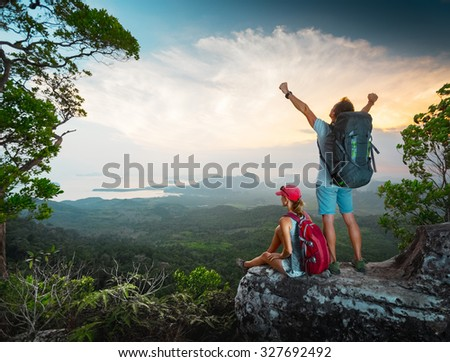 Two hikers relaxing on top of the mountain and enjoying sunset valley view - stock photo