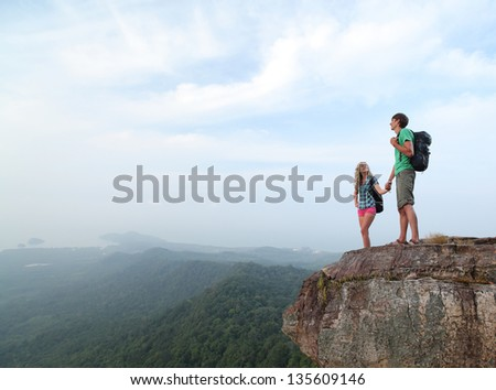 Two hikers standing on top of a mountain and enjoying valley view - stock photo