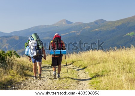 Two hikers tourists on a path in mountains