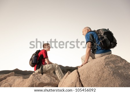 Two Hikers with Backpacks Relaxing on Boulders - stock photo