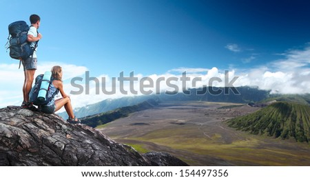 Two hikers with backpacks relaxing on top of a hill with valley view - stock photo