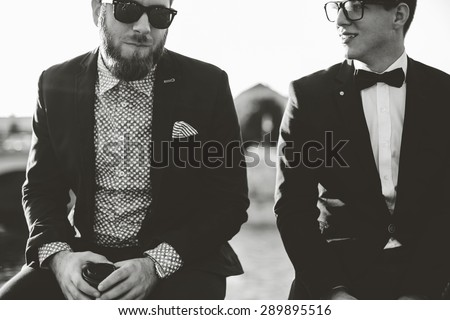 Two hipster friends having fun outside, drinking coffee and chatting, shallow depth of field, black and white  - stock photo