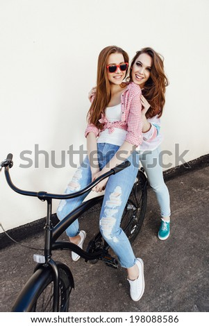 Two hipster girl friends with bicycle having fun. Outdoors, lifestyle.