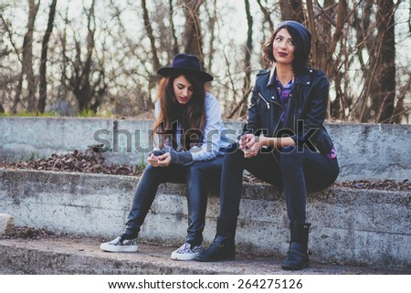 Two hipster girls away from the city crowd - stock photo