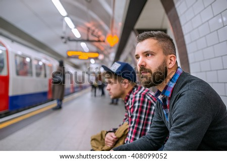 Two hipster men sitting at the underground platform waiting