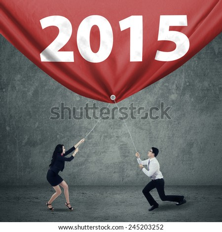 Two hispanic business team pulling number 2015, symbolizing a progress in 2015 - stock photo