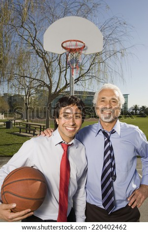 Two Hispanic businessmen on a basketball court - stock photo