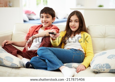 Two Hispanic Children Sitting On Sofa Watching TV Together - stock photo