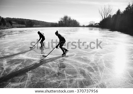Two hockey players during ice hockey game on natural ice