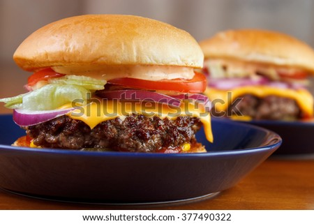 Two homemade burgers with cheese , lettuce, tomato and red onion - stock photo