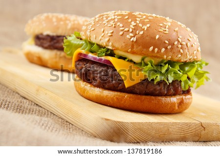 Two homemade grilled hamburgers on wooden board - stock photo