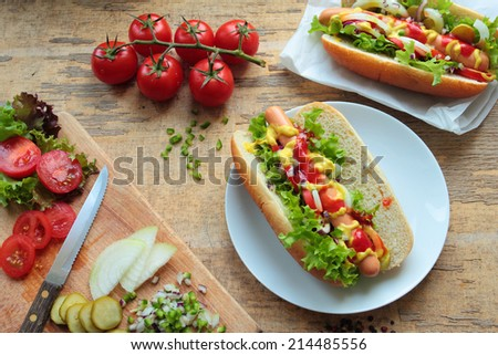 Two homemade hot dogs with sausages and fresh vegetables - stock photo