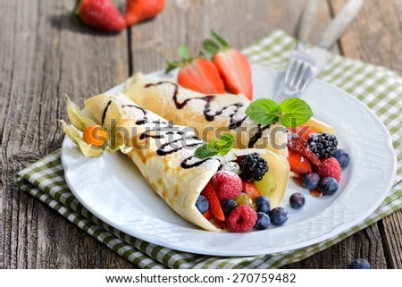 Two homemade pancakes stuffed with mixed berries  - stock photo