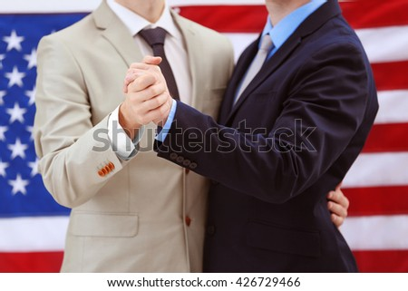 Two homosexuals dancing on American flag background - stock photo