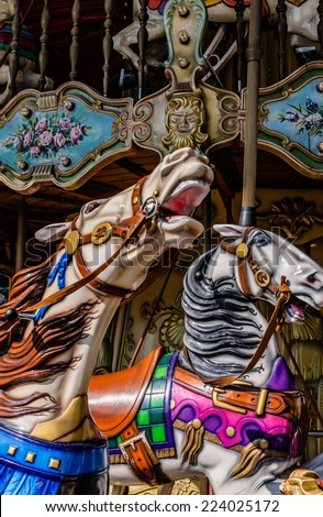 Two horses in a carousel in a fun park - stock photo