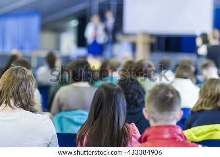 Two Hosts Speaking In front of the Large Group of People. Horizontal Image Composition - stock photo