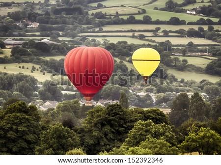 Two hot air ballons drifting across a rural landscape - stock photo