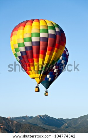 Two hot air balloons ascend over front range mountains during Colorado Springs' 2011 Balloon Classic - stock photo