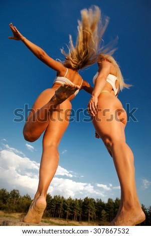 Two hot babes from back on the beach over blue sky background. - stock photo