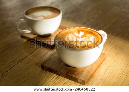 Two hot latte on wooden saucers and table with soft focus and shallow depth of field. - stock photo