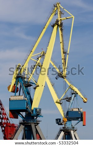 Two huge industrial cranes with blue sky at the background