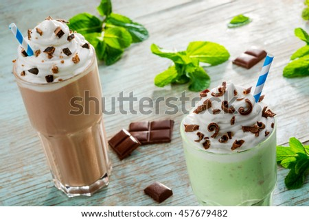 Two huge portions of milkshakes of different types. Cooling chocolate and mint drink with the adding of chocolate chips and cookie pieces. Juicy leaves of mint as the main ingredient. - stock photo
