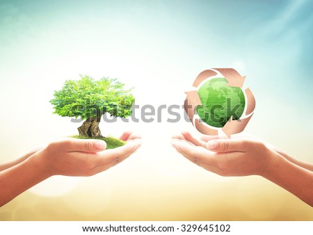 Two human hands holding big green tree and recycle arrow symbol made of old paper texture protecting green earth globe of grass over blurred nature. Saving world environmental, Clean Earth concept. - stock photo