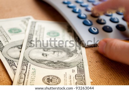 Two hundred-Dollar bills and male hand in motion, pressing keys on the calculator - stock photo