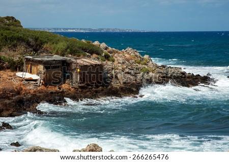 Two huts of palm leaves on the coastline of Crete near Malia - stock photo